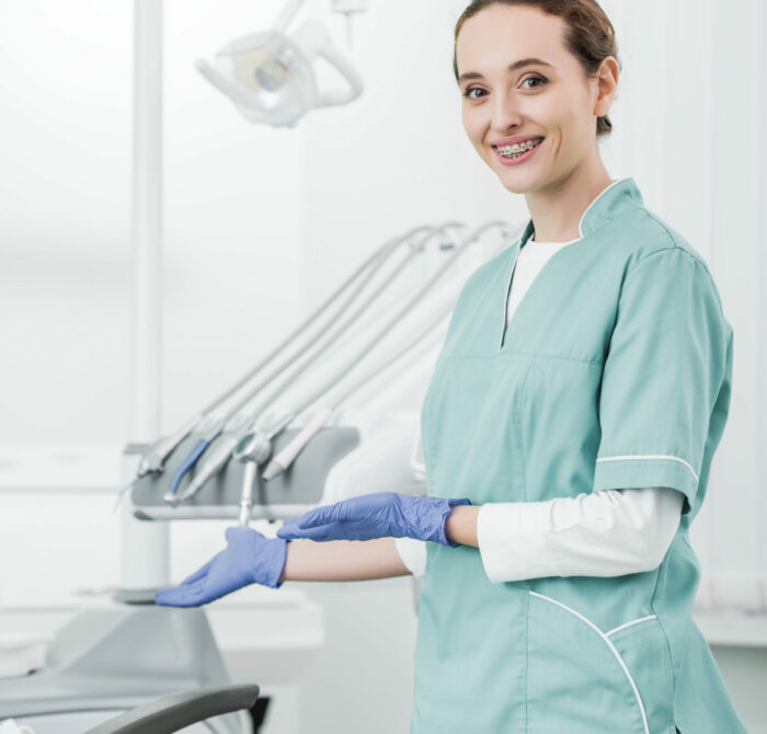 attractive dentist with braces on teeth smiling while gesturing in dental clinic